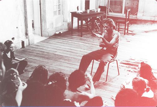 pessoa sentada de frente a uma turma aparentemente ensinando