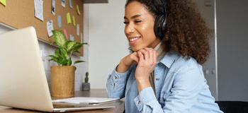 mulher negra ao telefone olhando para o notbook